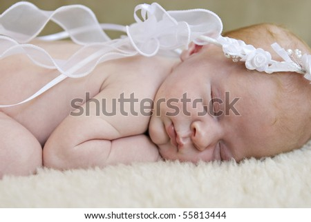 A beautiful angelic sleeping baby girl wearing white headpiece with ribbons, soft focus closeup