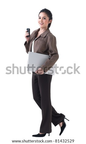 A beautiful asian  business woman walking with laptop and on the phone - stock photo