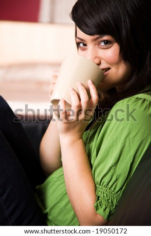A beautiful asian girl holding a cup of coffee - stock photo