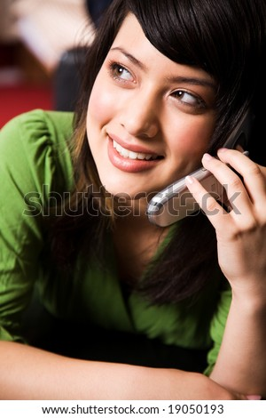 A beautiful asian girl talking on the phone - stock photo