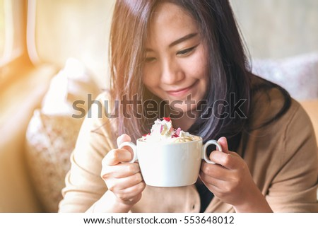 A beautiful asian woman and hot coffee with whipped cream topping in the cafe , feeling happy and smiley face