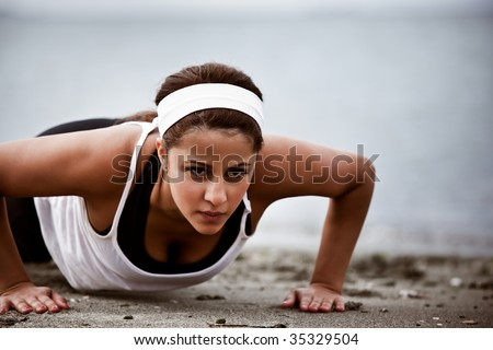 A beautiful asian woman doing push up at a beach - stock photo