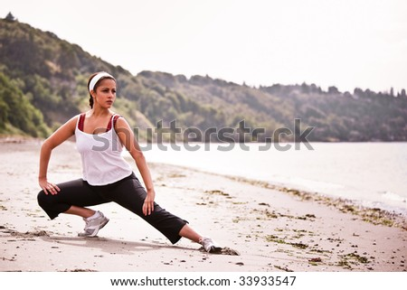 A beautiful asian woman exercises at a beach - stock photo