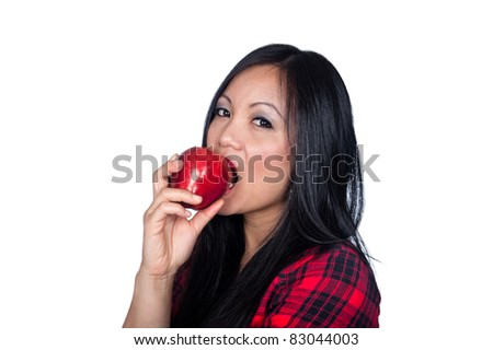 A beautiful Asian woman gets ready to eat an apple. - stock photo