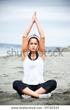 A beautiful asian woman practices yoga at a beach - stock photo