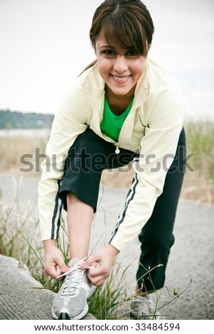 A beautiful asian woman tying shoelaces before exercising in a park - stock photo