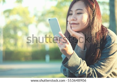 A beautiful asian woman using on the smart phone with feeling relax and smiley face ,  outdoor and green nature background