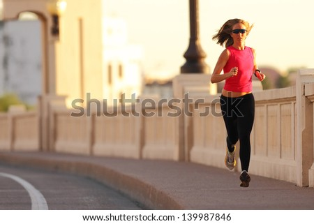 A beautiful athletic woman running in an urban environment - stock photo