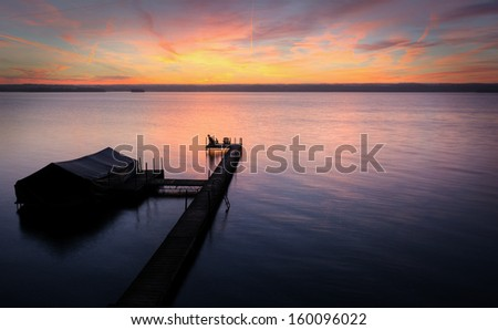 A beautiful autumn sunrise on the shores of Lake Cayuga in the Finger lakes region of New York state.  The pier leads out to a power boat shelter and a deck with chairs for watching the sunrise.