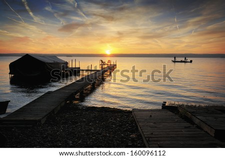 A beautiful autumn sunrise on the shores of Lake Cayuga in the Finger lakes region of New York state. A row boat is docked on the side of a pier. Two fisherman enjoy the sunrise from their boat. - stock photo