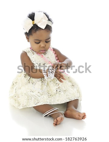 A beautiful baby girl all dressed up, examining the bracelet of beads she wears on her wrist.  On a white background. - stock photo