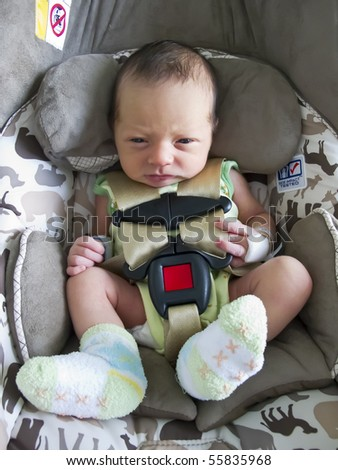 A beautiful baby photographed in a infant car seat - stock photo