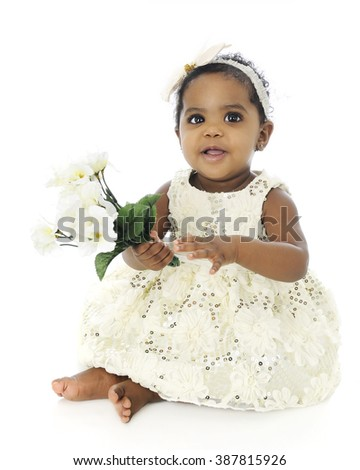 A beautiful, barefoot baby girl in a white hair bow and sequin dress.  She's happily holding a small bouquet of white flowers.  On a white background. - stock photo