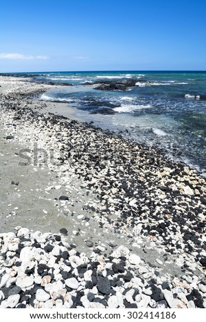 A beautiful black and white gravel beach with clear blue water on a remote beach in Kona Hawaii. - stock photo