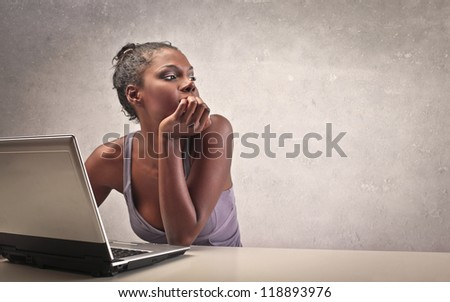 A beautiful black girl, while is using a laptop computer, thinks - stock photo