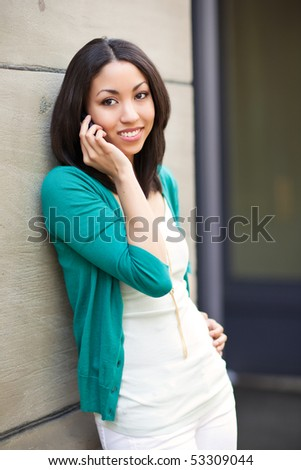 A beautiful black woman talking on her phone - stock photo