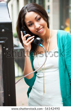 A beautiful black woman talking on the public phone - stock photo