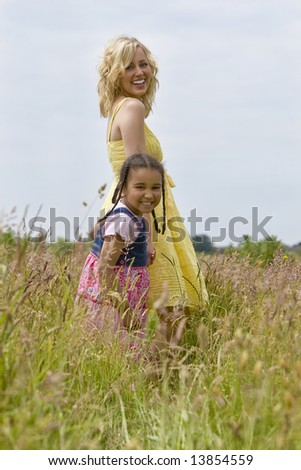 A beautiful blond haired blue eyed young woman having fun walking through a field of long grass with a mixed race young girl