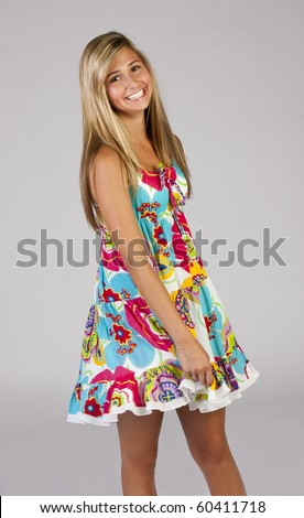 a beautiful blond teenage girl wearing a colorful party dress.
