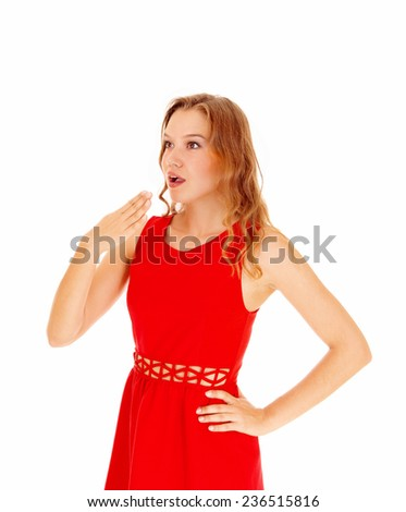 A beautiful blond young woman holding her hand for her mouth, she is surprised what she sea's, isolated for white background.  - stock photo