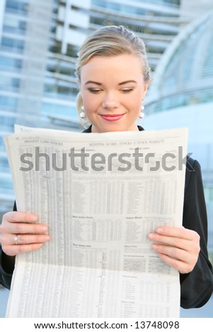 A beautiful blonde business woman in front of office building reading newspaper - stock photo