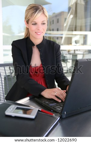 A beautiful blonde business woman on laptop computer