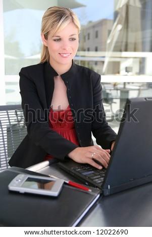 A beautiful blonde business woman on laptop computer - stock photo