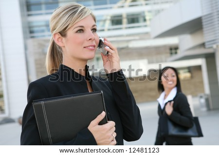 A beautiful blonde business woman on the phone at work - stock photo