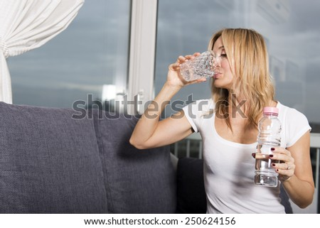 a beautiful blonde girl drinking water.