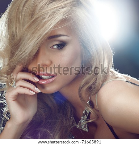 A beautiful blonde woman on black background - stock photo