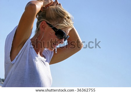a beautiful blonde woman outside at the beach is fixing her hair, wearing sunglasses, large hoop earrrings and a shiny tee shirt with space for copy or text - stock photo