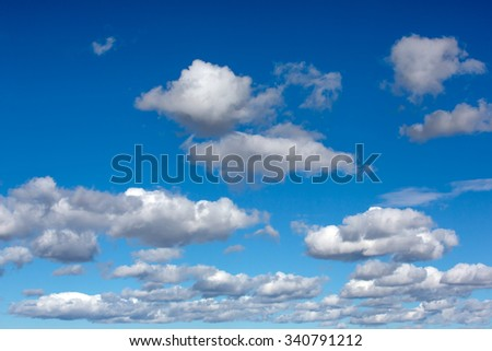A beautiful blue sky filled with white fully clouds. - stock photo