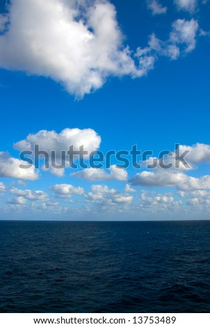 A beautiful blue sky over a calm sea with white clouds
