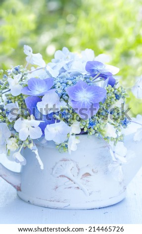 a beautiful bouquet of hydrangea blossoms in a blue terracotta vase - stock photo