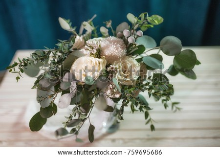 A beautiful bouquet of white roses, chrysanthemums, eucalyptus branches, brunia