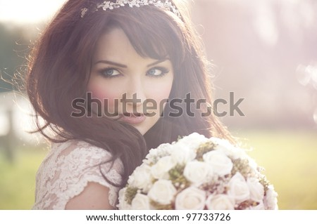 A beautiful bride looking to the side outdoors. - stock photo