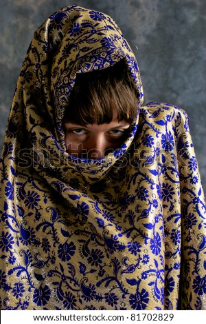 A beautiful brown haired woman is looking at viewer, most of her face and head is covered with exotic shawl. - stock photo