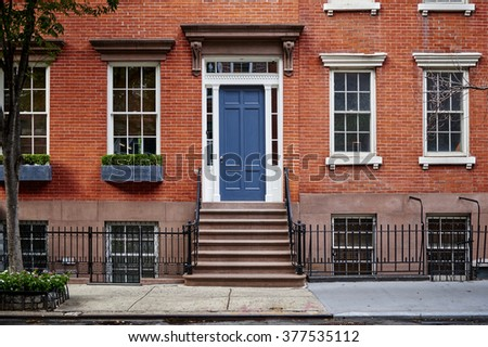 a beautiful brownstone townhouse with a blue door - stock photo