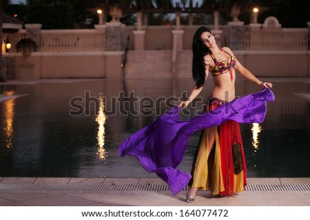 A beautiful, brunette belly dancer wearing a red costume dancing with a purple silk veil. She is at an upscale, Mediterranean style resort with a swimming pool in the background.