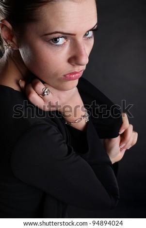 A beautiful brunette girl posing in a studio wearing a black dress.Close up. - stock photo
