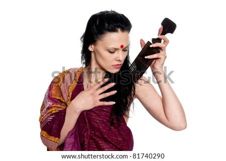 A beautiful brunette in the Indian sari combs comb hair posing in studio on white background - stock photo
