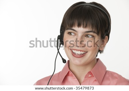 A beautiful brunette talking into a headset.  She is smiling,  Horizontally framed shot.