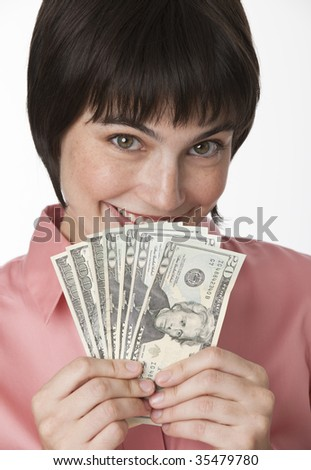 A beautiful brunette woman holding a fanned-out stack of cash.  She is smiling.  Vertically framed shot. - stock photo
