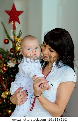 A beautiful brunette young mother holding her little baby against the Christmas Tree - stock photo