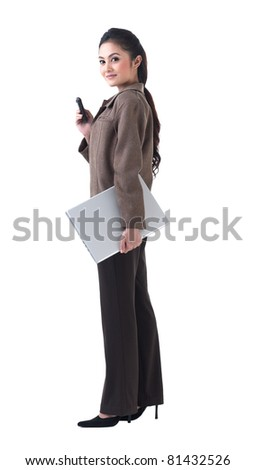 A beautiful business woman standing with laptop and on the phone - stock photo