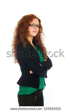 A beautiful business woman with natural red hair wearing a suit and crossing her arms. - stock photo