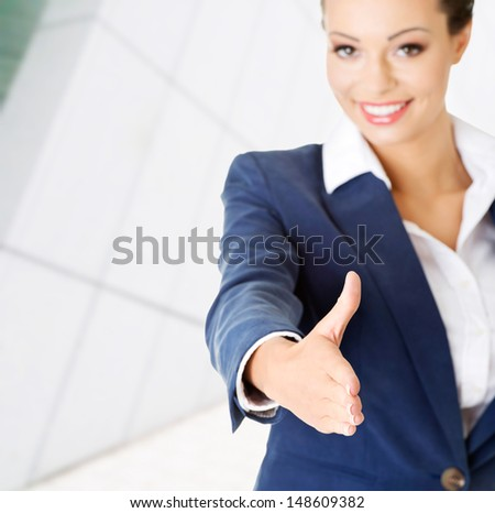 A beautiful businesswoman about to shake hands. - stock photo