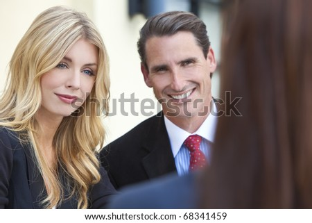 A beautiful businesswoman in a meeting with her male and female colleagues - stock photo