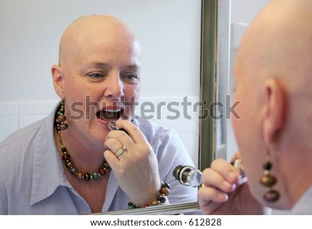 A beautiful cancer survivor applying makeup and getting ready to go out. - stock photo