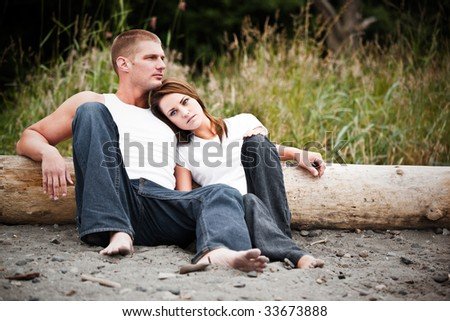 A beautiful caucasian couple in love sitting on the beach - stock photo